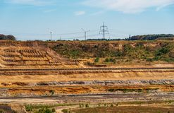 View to the edge of a lignite mining area with conveyor belts, wind power wheels in background. Etzweiler, Rhenish lignite mining area stock photos