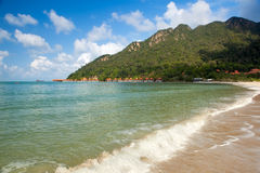 View to the empty tropical island beach under waves. With and hotel near mountain, Langkawi, Malaysia Stock Photo