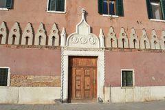 Ancient house with enormous wooden main door at the Italian Venice seafront of the Venice lagoon. royalty free stock images