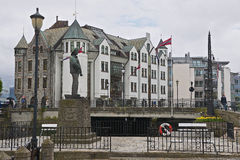 View to the Fisher Boy statue with old building at the background in Alesund, Norway. Stock Photo