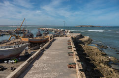 View to fishing boats in Essaouira harbour and cannons in Skala stock photography