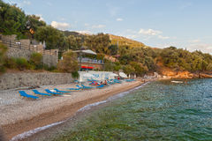View to Glyfa beach with tourist on lounge chairs Stock Photo