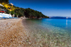 View to Glyfa beach with tourist on lounge chairs and swimming Royalty Free Stock Image