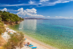 View to Glyfa beach with tourist on lounge chairs and swimming Royalty Free Stock Photos