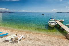 View to Glyfa beach with tourist on lounge chairs and swimming Stock Photos
