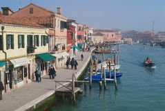 View to the Grand canal, boats, buildings and people at the street in early spring in Murano, Italy. Stock Photography