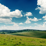 View to green hills and deep blue sky with low clouds Stock Photography