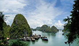 View to green mountain in  Ha Long bay. View to green mountain in Ha Long Bay , many tourist boats near high mountain,blue sky with white clouds . Vietnam Royalty Free Stock Photography