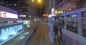 View to Hong Kong from moving double-decker tram. HONG KONG - NOVEMBER 09, 2015: Traveling in evening city in double-decker tram. Tramway arriving to the station stock footage