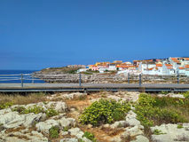 View to houses near ocean and wooden road in Peniche Stock Images