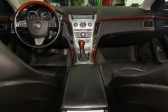 View to the interior of Cadillac CTS with dashboard, clock, media system, front seats and shiftgear after cleaning before sale on stock photos