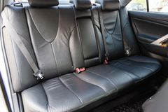 View to the interior of car with dashboard, rear seats, black leather after cleaning before sale on parking stock photos
