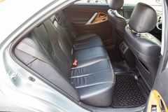 View to the interior of car with dashboard, rear seats, black leather after cleaning before sale on parking royalty free stock photography