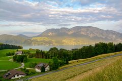 View to lake Attersee with green pasture meadows and Alps mountain range near Nussdorf Salzburg, Austria stock image