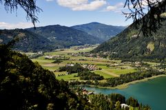 View to Lake Ossiach, Carinthia, Austria. Image shows a panoramic view to Carinthia, Austria. On the right there is a part of Lake Ossiach, some meadows and Stock Photography