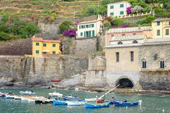 View to a little port on sea, buildings and mountains. View to a little port with boats on sea, buildings and mountains. Vernazza, Cinque Terre, Italy stock photo