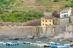 View to a little port on sea, buildings and mountains. View to a little port with boats on sea, buildings and mountains. Vernazza, Cinque Terre, Italy royalty free stock image