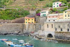View to a little port on sea, buildings and mountains. View to a little port with boats on sea, buildings and mountains. Vernazza, Cinque Terre, Italy royalty free stock images