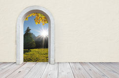 View to Nature from a empty room with arched door. Back to nature, room with wooden rustic floor and beige colored wall with plastering, open gate with view to Stock Photos