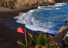 View to ocean and beach with red flag. Tenerife Royalty Free Stock Photo