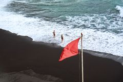 View to ocean and beach with red flag. View to ocean and beach with red flag and two people Stock Photography
