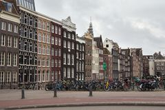AMSTERDAM, NETHERLANDS - JUNE 25, 2017: View to the old historical dutch buildings in Amsterdam. View to the old historical dutch  buildings and bicycles Stock Photos