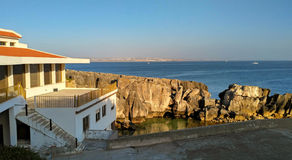 View to old houses on cliff near the ocean in sunset light, Peniche Royalty Free Stock Images