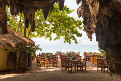 View to open-air restaurant on beach from cave Royalty Free Stock Photo