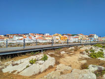 View to Peniche houses near ocean and wooden road Stock Photos