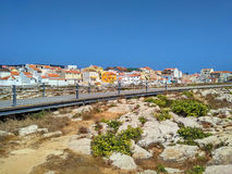 View to Peniche houses near ocean and wooden road Stock Images