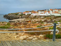 View to Peniche houses near ocean from wooden road Stock Photography