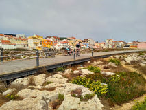 View to Peniche houses near ocean and wooden road Stock Photography