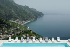 View to pool and sea. View to pool,chaise longues and sea. Italy Stock Photo