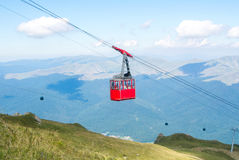 A view to red open cableway cabin over the top of the mountain a Royalty Free Stock Photo