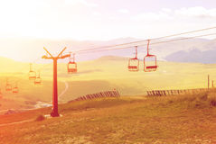 A view to red open cableway cabin over the top of the mountain a Royalty Free Stock Images