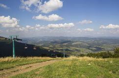 A view to red open cableway cabin over the top of the mountain and buautiful landscapes with blue mountains, green Stock Photos