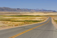View to the road and mountain range at Shoshone, USA Stock Photos