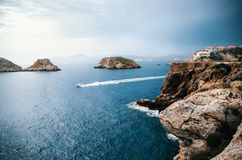 View to rocks of Santa Ponsa in Mallorca island before the storm. The yacht sails near the rocks of Santa Ponsa in the mediterranean sea before the storm Royalty Free Stock Photography
