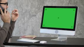 Business, deadline and technology concept - man with computer calling on smartphone and pointing to the monitor. Green. View to the screen of computer. Business stock video