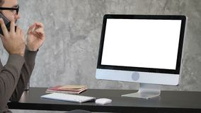 Business, deadline and technology concept - man with computer calling on smartphone and pointing to the monitor. White. View to the screen of computer. Business stock footage