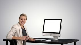 Confident focused businesswoman talking to camera and looking to monitor near her on gradient background. View to the screen of computer. Confident focused stock video