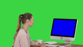 Girl sitting in front of the computer monitor and watching something smiling blue screen mock-up display on a green. View to the screen of computer. Girl sitting stock video
