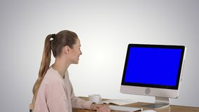 Girl sitting in front of the computer monitor and watching something smiling Blue Screen Mock-up Display on gradient. View to the screen of computer. Girl stock video