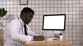 Medical doctor taking notes looking up info on his computer. White Display. View to the screen of computer.Medical doctor taking notes looking up info on his stock footage