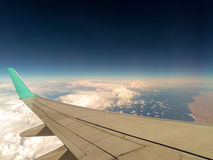 A view to the sea from the airplane window during the flight above the clouds Stock Photography