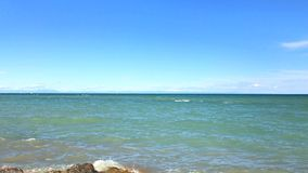 View to sea line at sunny day: wave splash near stone shore. View to sea line and clear sky at sunny day: sea wave splash with drops near wet stone shore, white stock footage