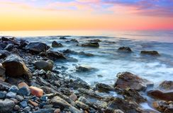 The view to the sea and nice sunset with interesting sky is opened from the coast with rocks. Beautiful summer landscape Stock Photos