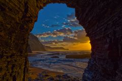 View to the sea sunset from inside a cave at Barriga Beach, Port Stock Images