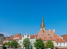 A view to the Sibiu little square and Lutheran Cathedral of Saint Mary in the Transylvania region, Romania.  stock photos