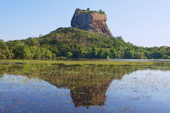 View to the Sigiriya rock fortress with reflection in water in Sigiriya, Sri Lanka. Stock Image